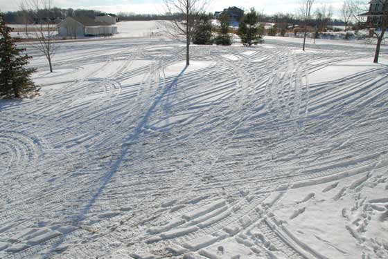 Snowmobile tracks in the yard