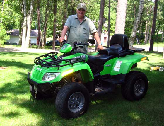 Curt Asche and his 2007 Arctic Cat TRV ATV with 50,000 miles.