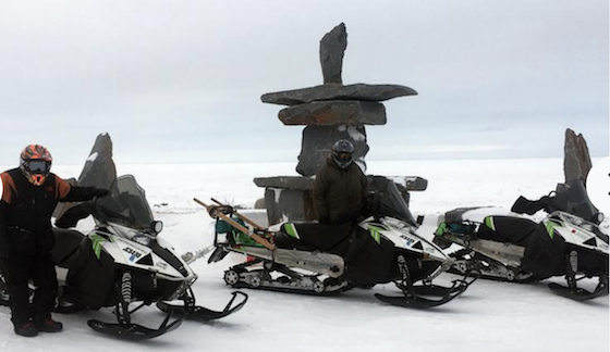 Paul Dick of Grand Rapids, Minn. (left), and Rex Hibbert of Henry, Idaho pause by a large Inukshuk, an Inuit landmark, Thursday, March 7, on the shore of Hudson Bay near Churchill, Man. Along with Rob Hallstrom of Park Rapids, Minn., the trio snowmobiled nearly 3,000 miles during a recent trek to Churchill and back from Grand Rapids. (Photo courtesy of Rob Hallstrom)