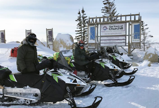 Rex Hibbert and Paul Dick pose by a sign March 6 welcoming visitors to Churchill, Man. (Photo courtesy of Rob Hallstrom)