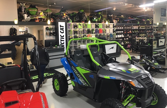 An SVX 450 snowbike and many other significant Arctic Cat snowmobile models line the ceilings near the parts counter