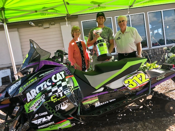 In July, Bernice and Roger Skime stand with 2020 Pro Stock Points champ Zach Herfindahl